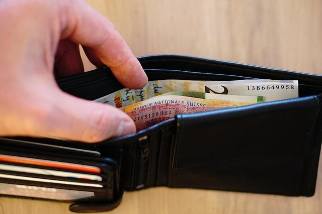 bankovky v černé peněžence, ruka
